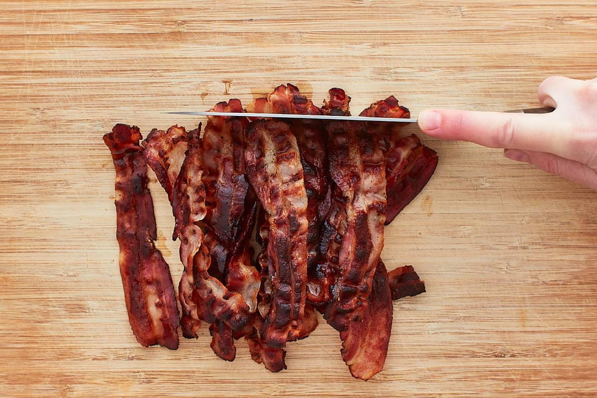 Cutting bacon into pieces with a long knife