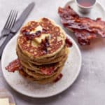 Stack of pancakes with bacon sprinkled on top