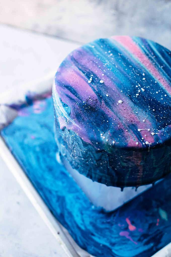 Mirror glaze dripping off the mirror glaze galaxy cake shown from above