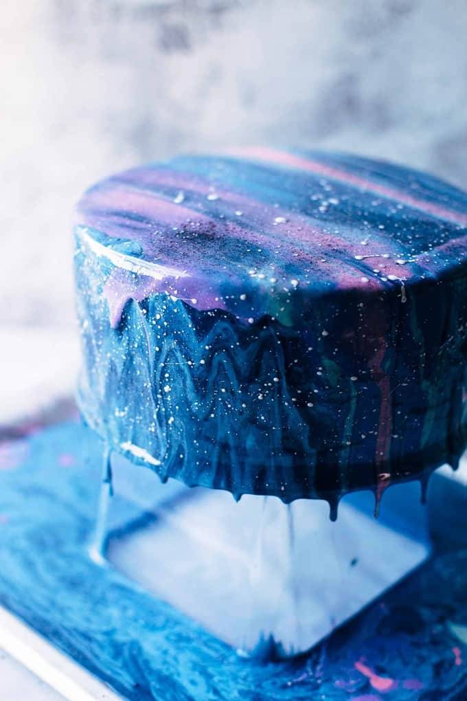 Colorful mirror glaze dripping off the baked cake onto a tray underneath