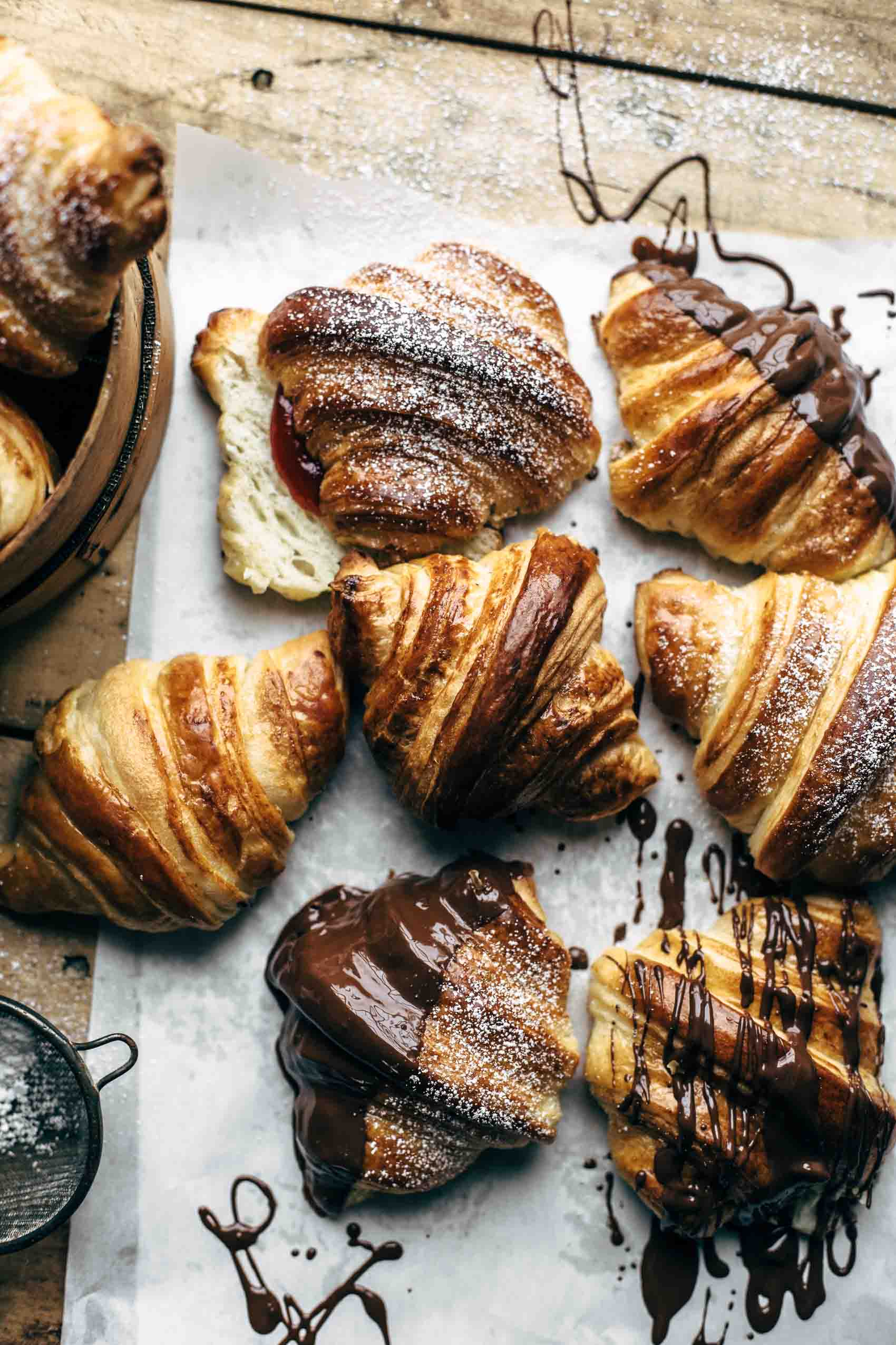 Baked croissants topped with powdered sugar and some dipped in chocolate on white paper