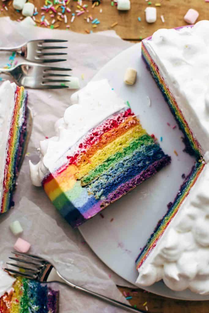Sliced rainbow cake on a cake plate