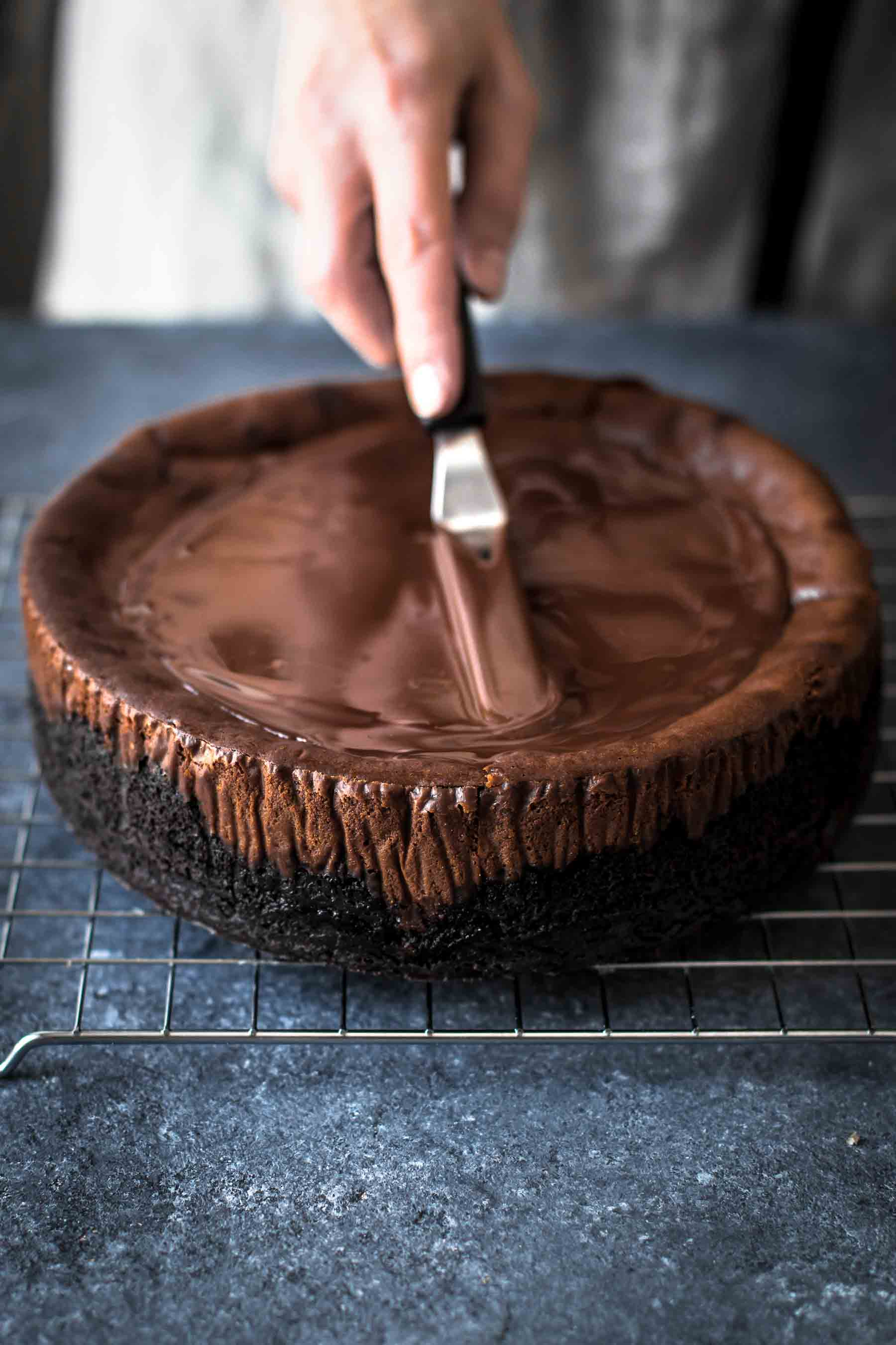 spreading chocolate ganache on top of chocolate cheesecake
