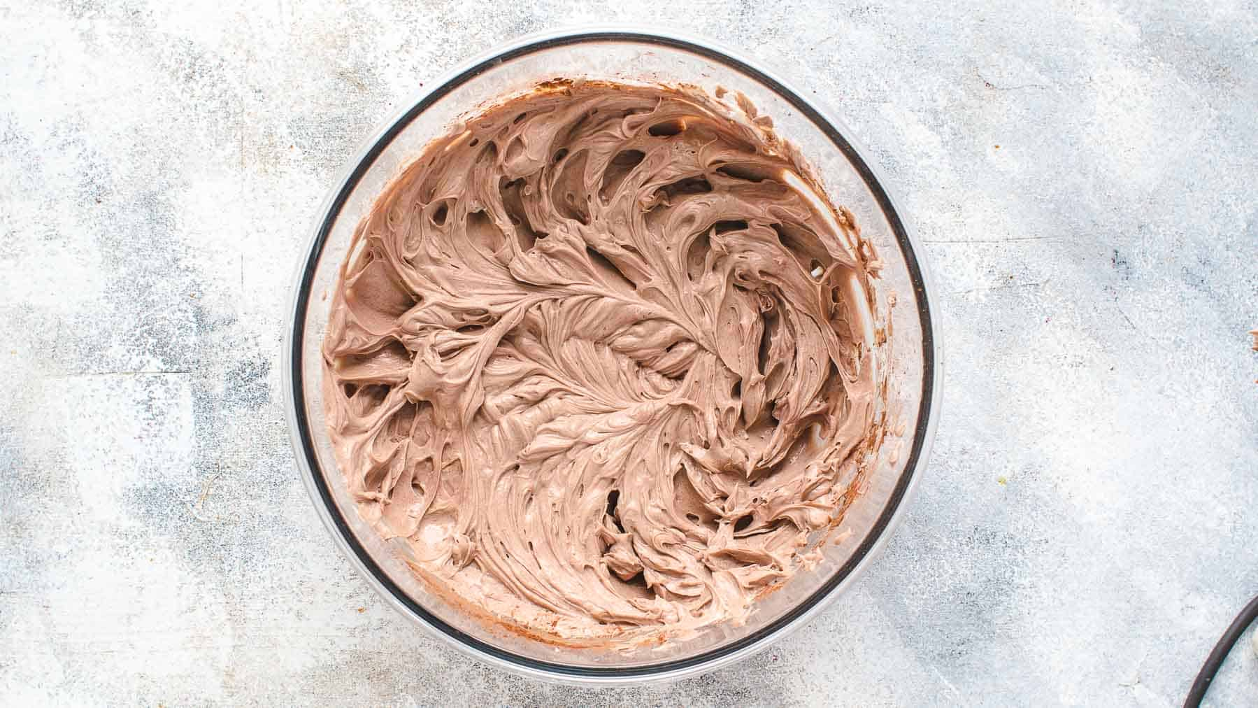 cocoa, sugar, and cream cheese mixed together in a mixing bowl