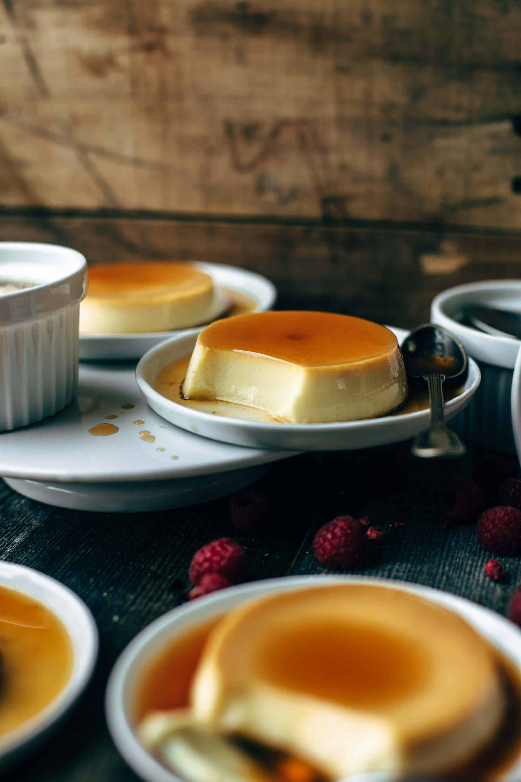 Picture of Spanish flans on white plates with spoons