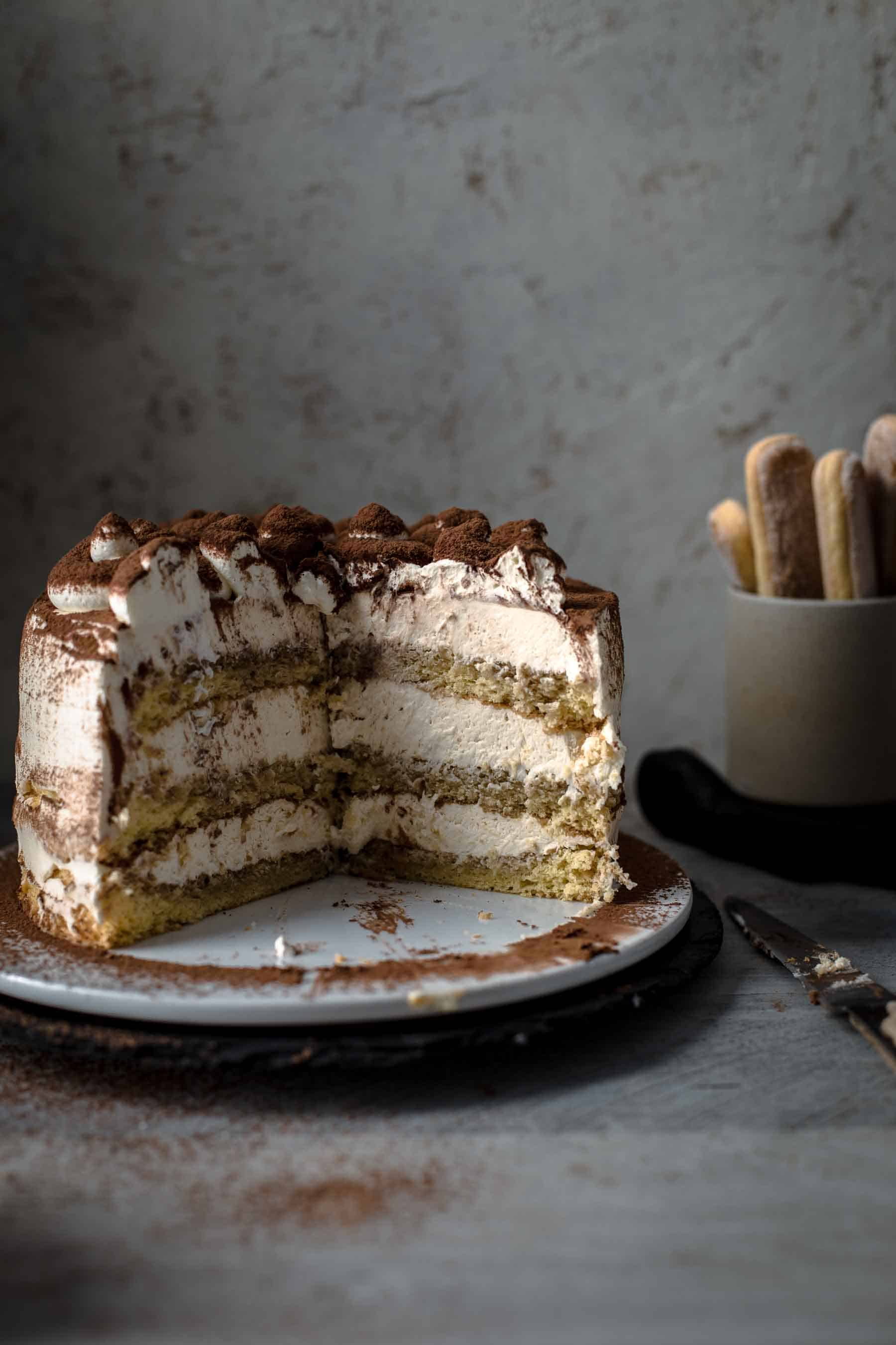 Cut Tiramisu Cake on serving plate.