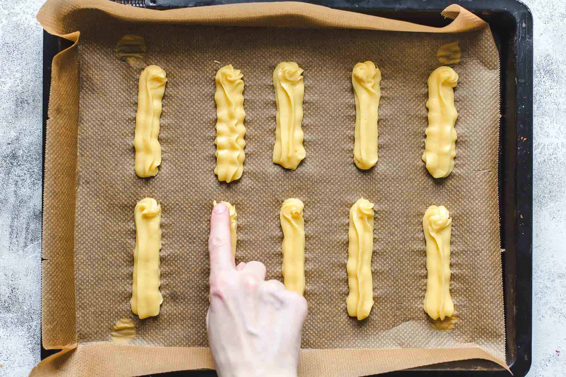 pressing down the tip of the puff pastry with wet finger