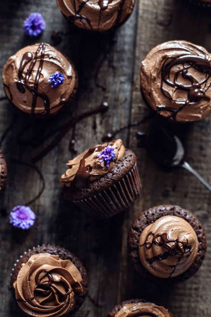Brownie cupcakes with chocolate and flower decoration on a wooden board