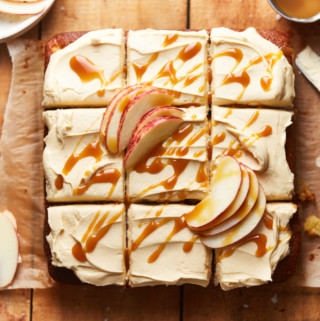 Sliced apple cake topped with frosting, caramel sauce, and apple slices on a table