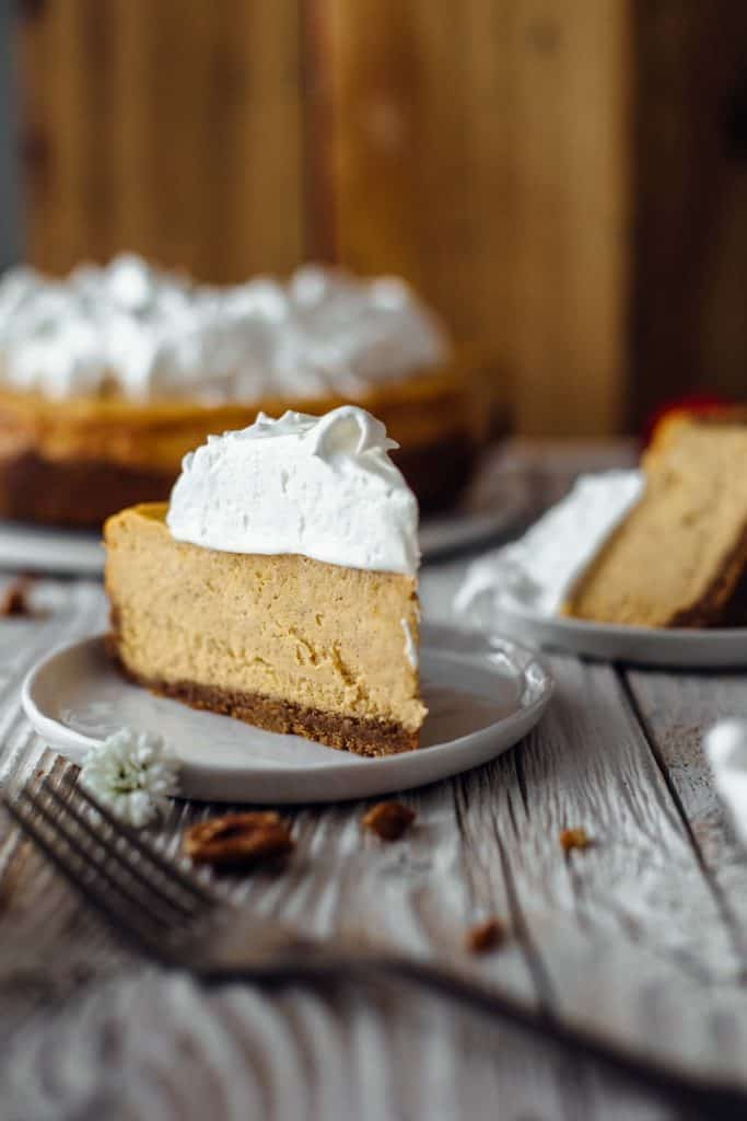 A slice of sweet potato cheesecake on a dessert plate topped with meringue