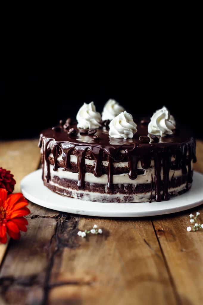 Decorated chocolate cake on a cake plate with dollops of whipped cream on top