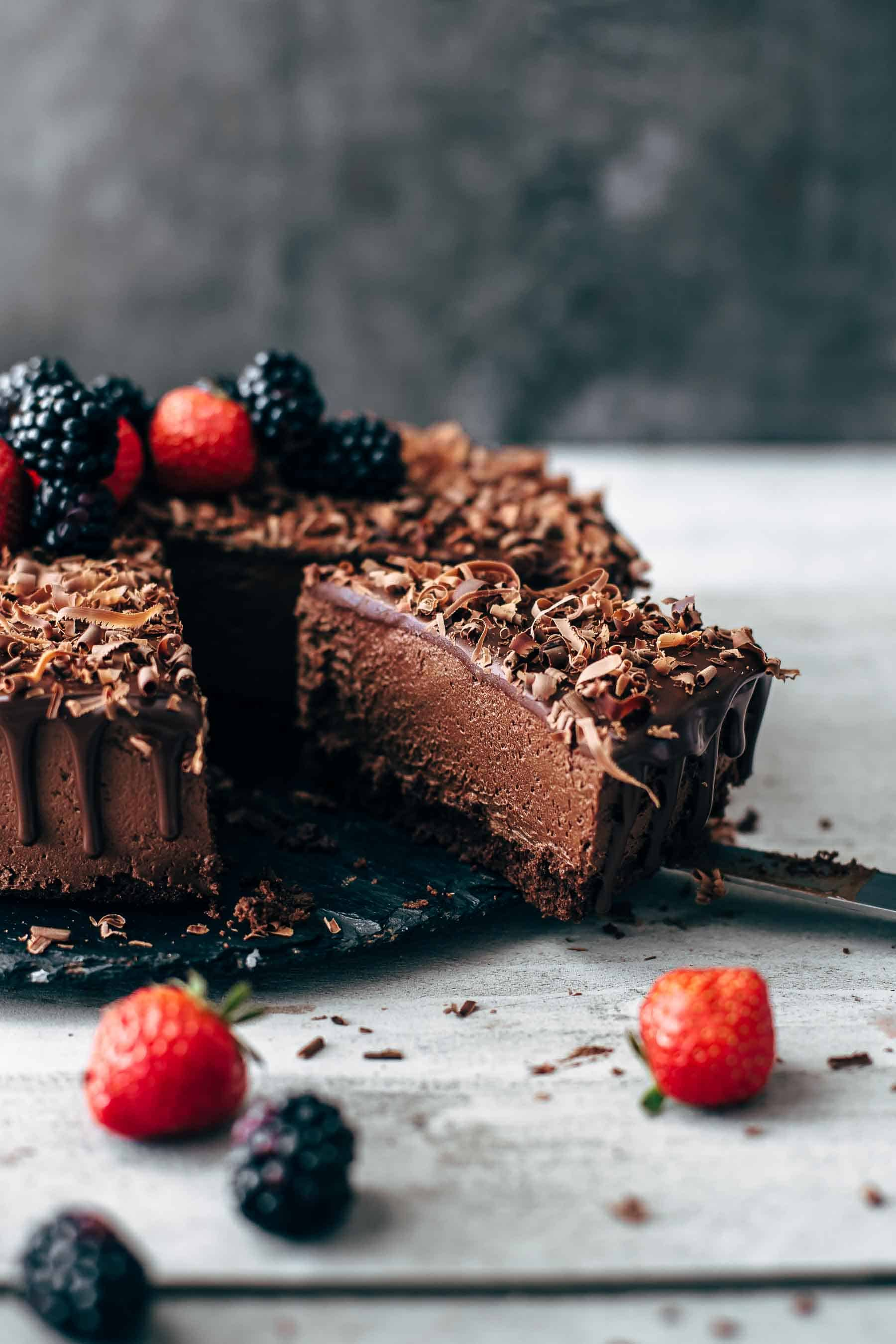 Cut chocolate mousse cake slice decorated with berries on grey background
