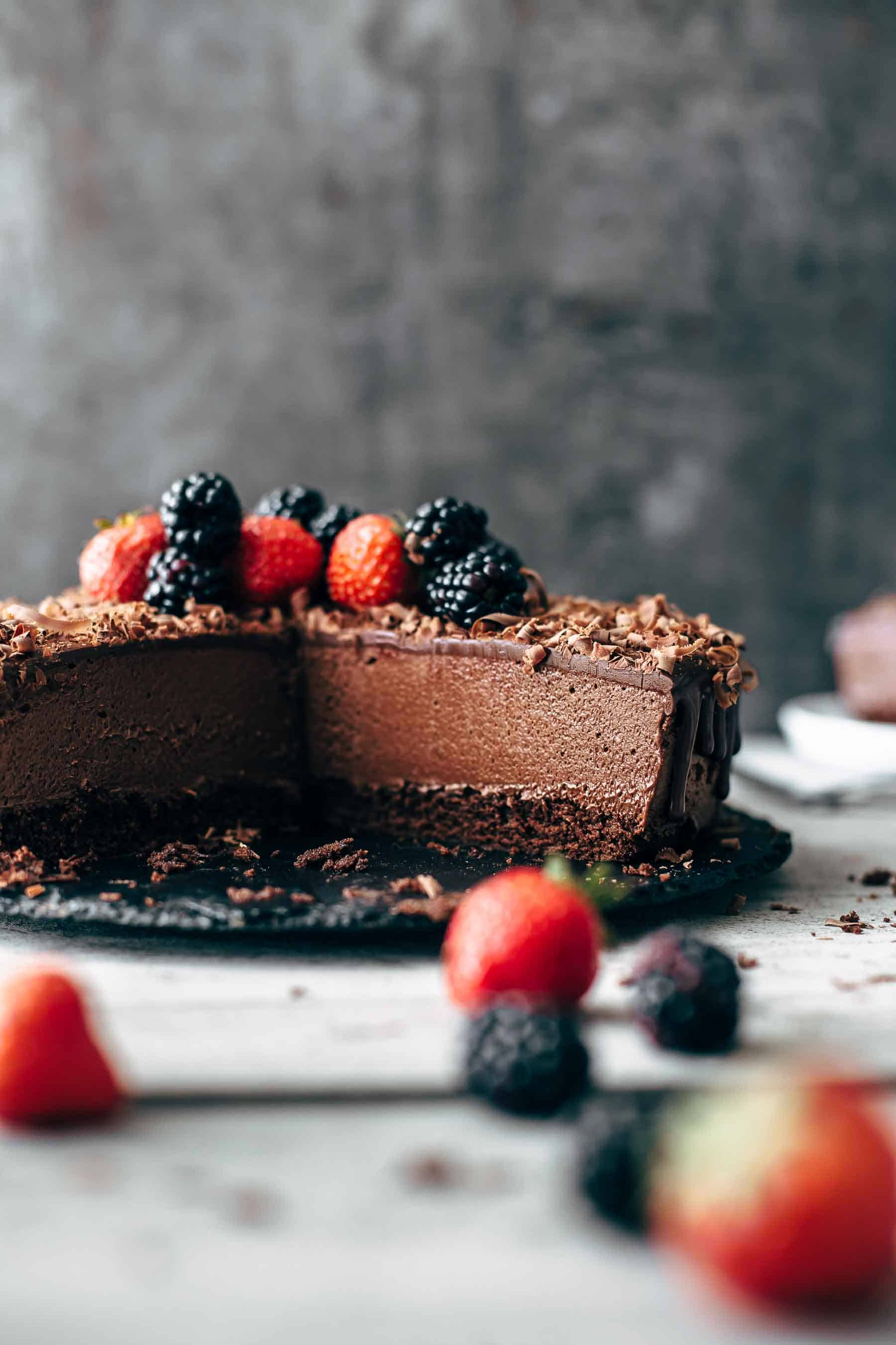 Cut chocolate mousse cake with berries on top on black serving plate