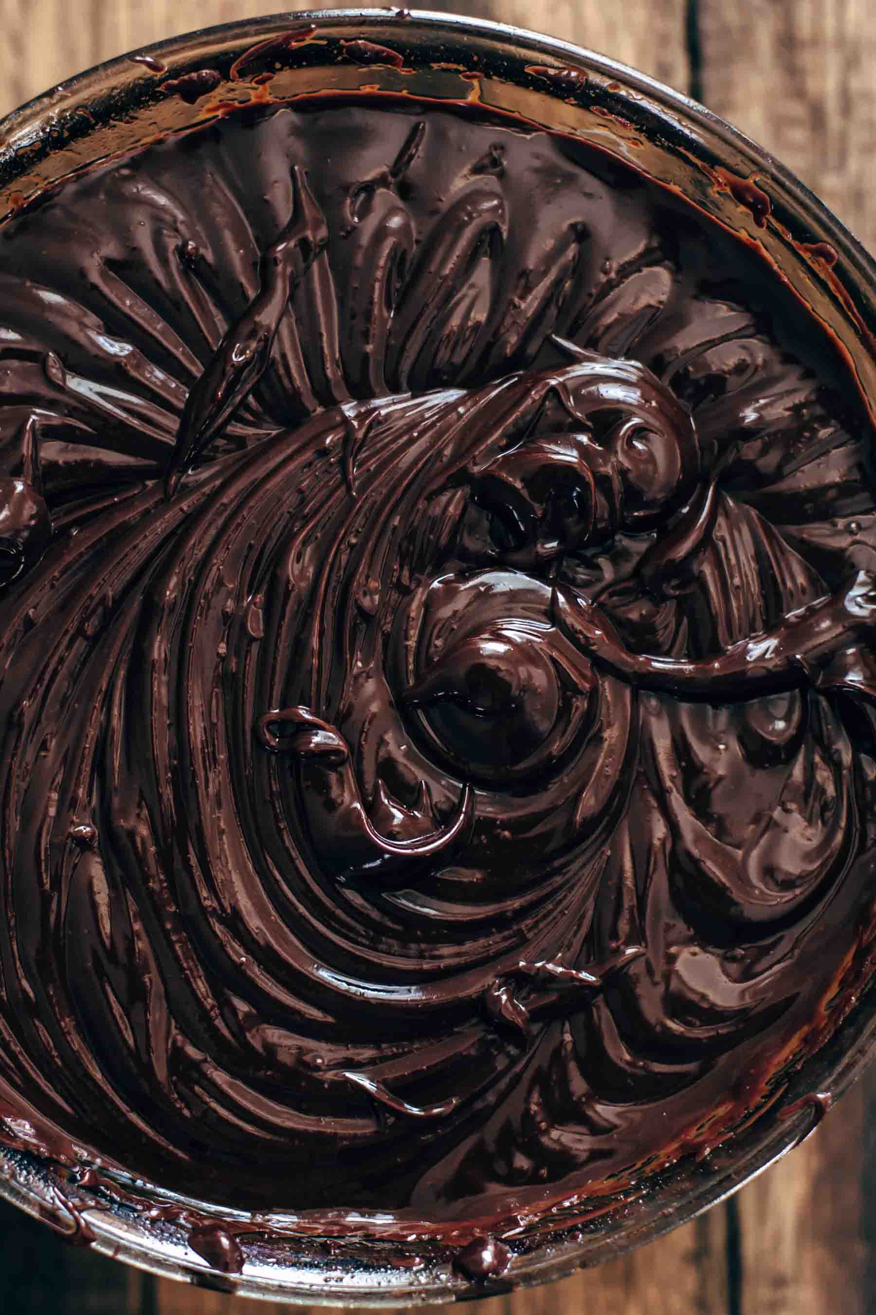 Whipped chocolate ganache in glass bowl on wooden surface