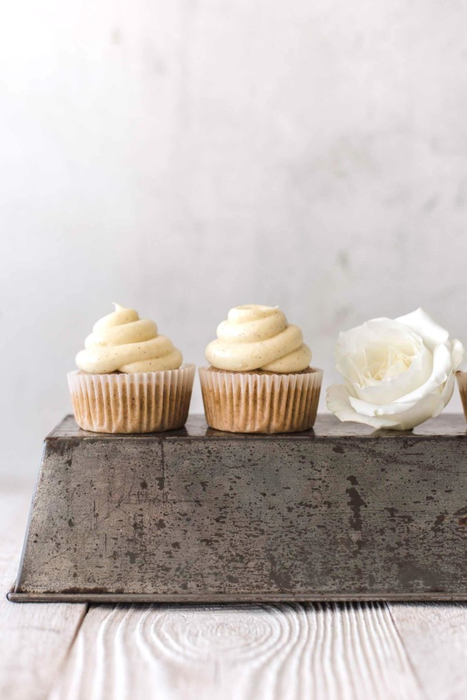 Two banana cupcakes on a baking tin with a white rose next to them