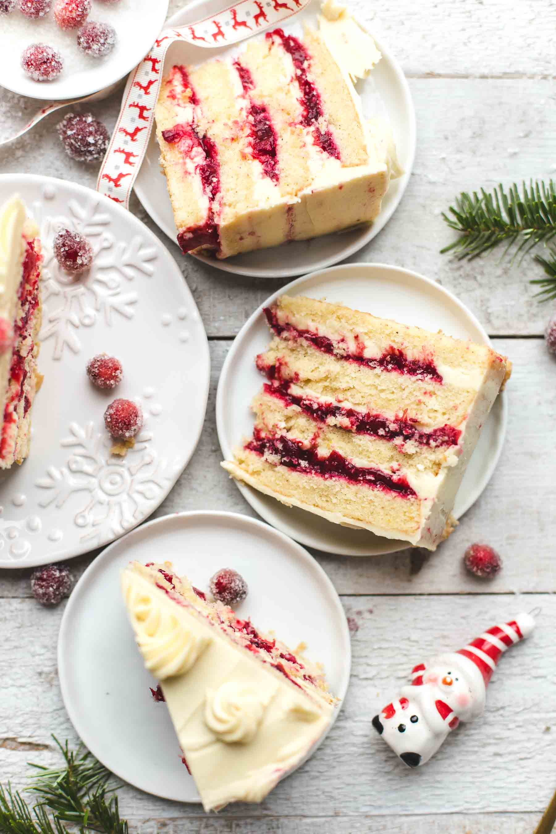 Different slices of Cranberry Orange Cake with White Chocolate Frosting on different plates