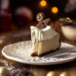 A slice of Baked Eggnog Cheesecake with Gingerbread Crust with a bite