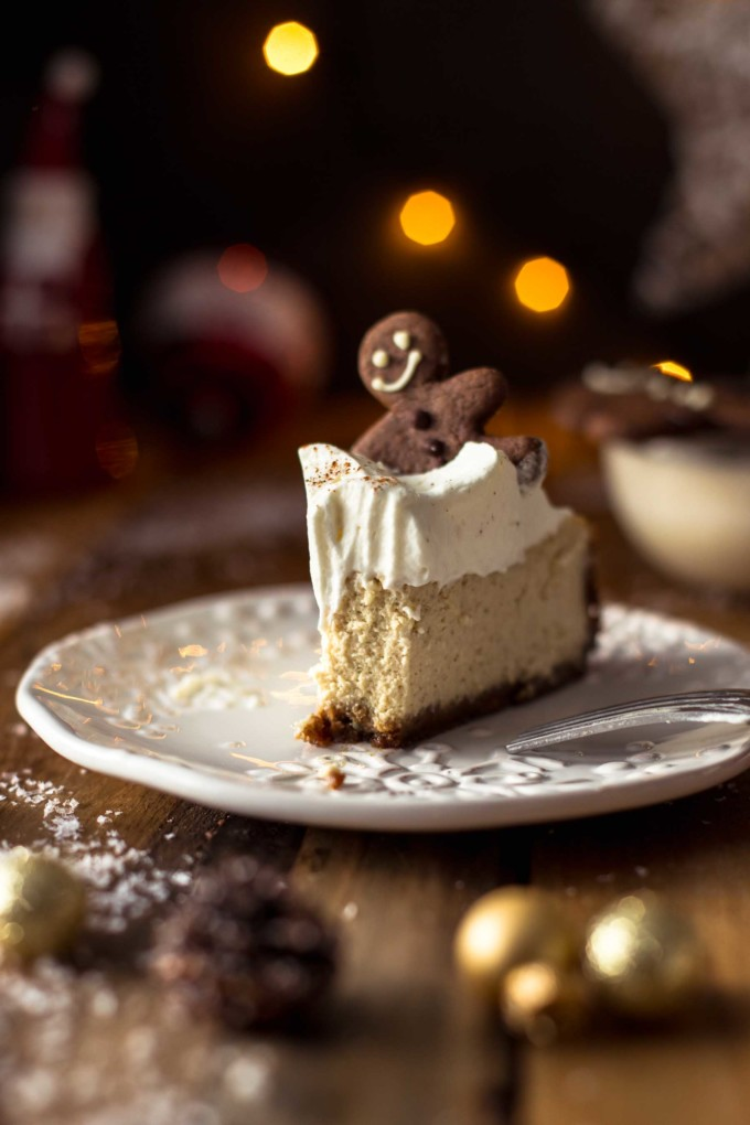 Half eaten cheesecake on a plate with a gingerbread and whipping cream decoration on top