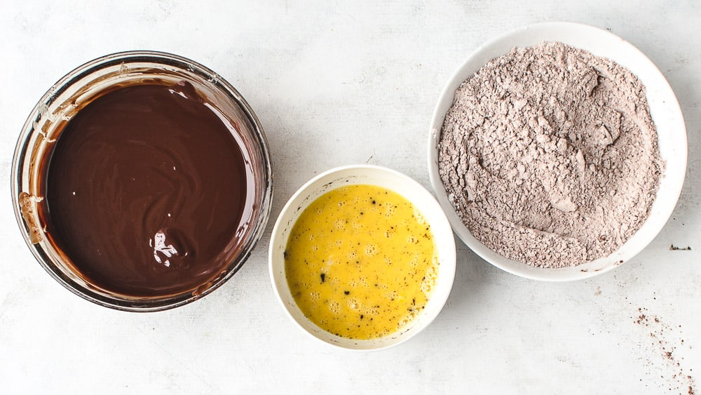 Three bowls with ingredients for mini chocolate cakes