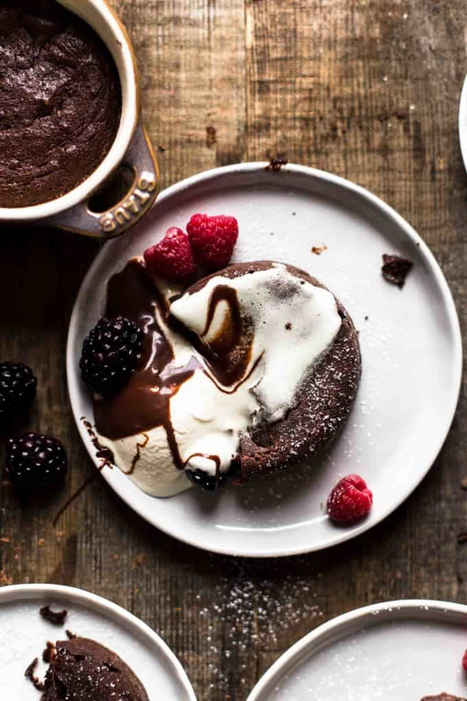 Half eaten chocolate cake on a dessert plate with whipped topping and berries on top