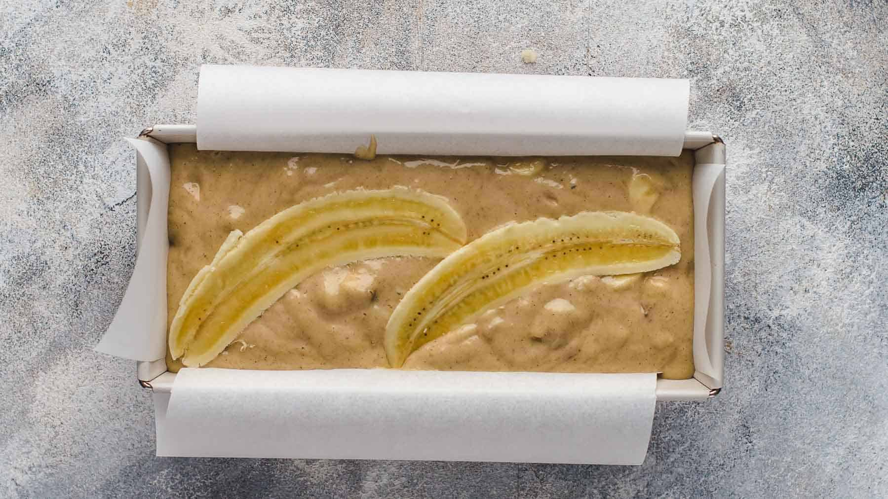 banana bread batter with banana on top in loaf pan