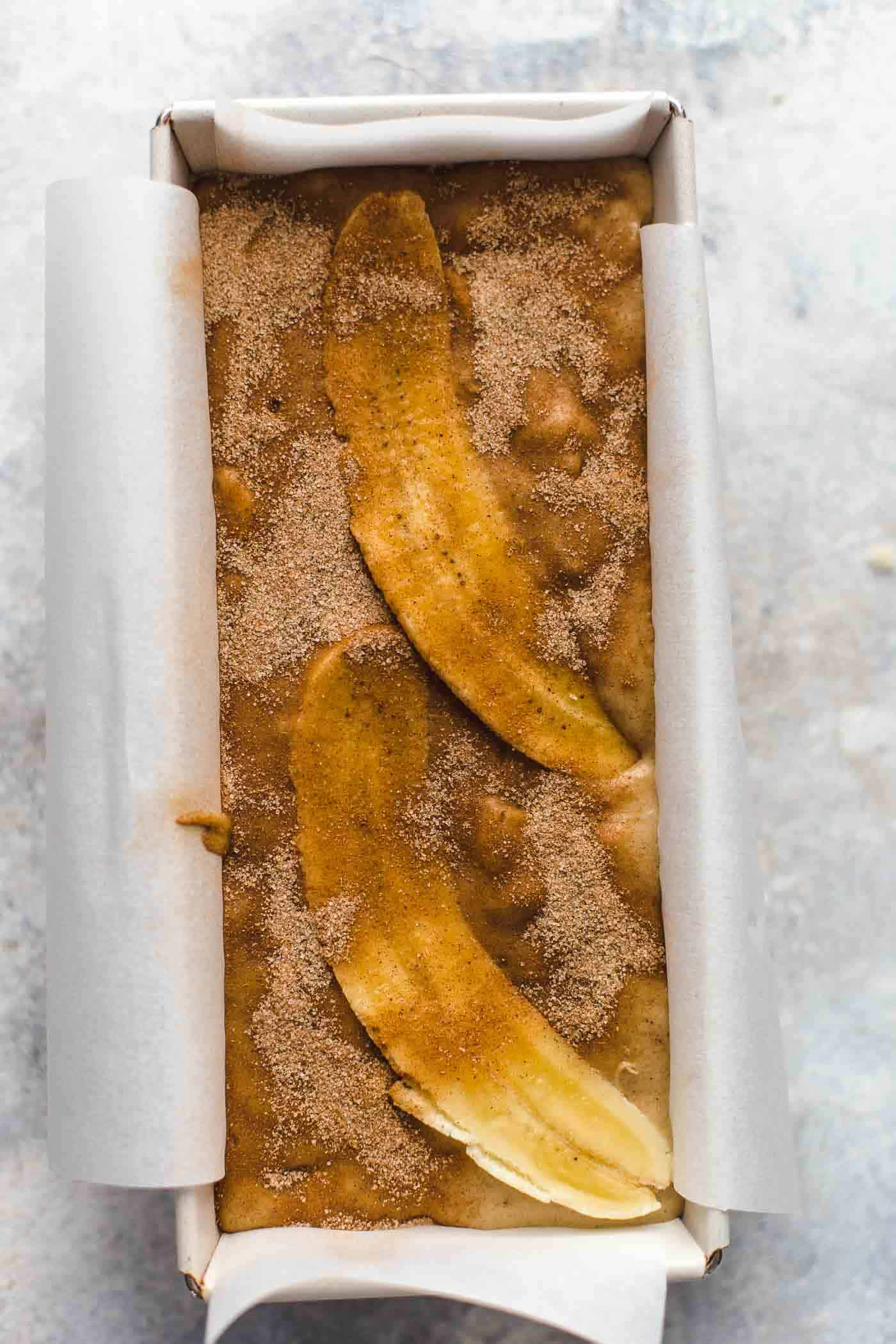banana bread batter with bananas and sugar on top