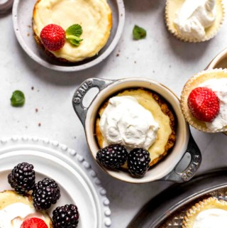 mini cheesecakes decorated with berries and whipped cream