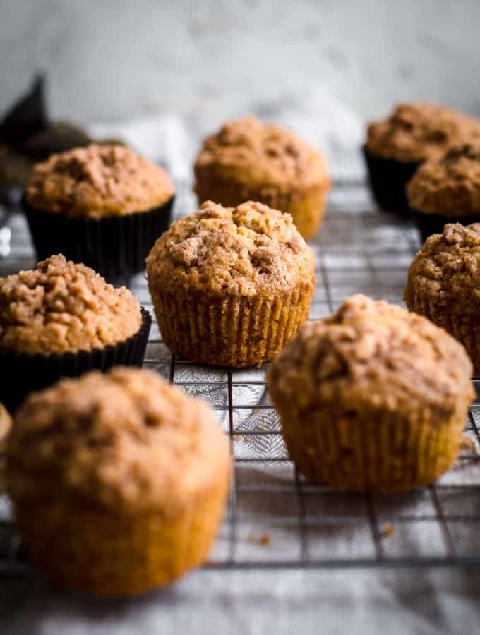 Carrot cake muffins arranged on cooling rack with a napkin underneath