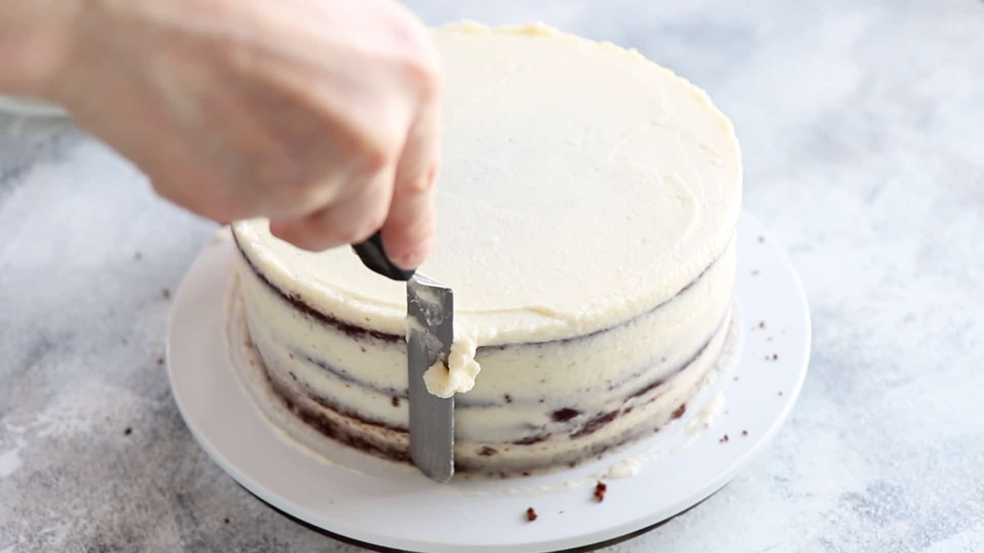 Leveling the sides of the chocolate cake with coconut frosting with an offset spatula