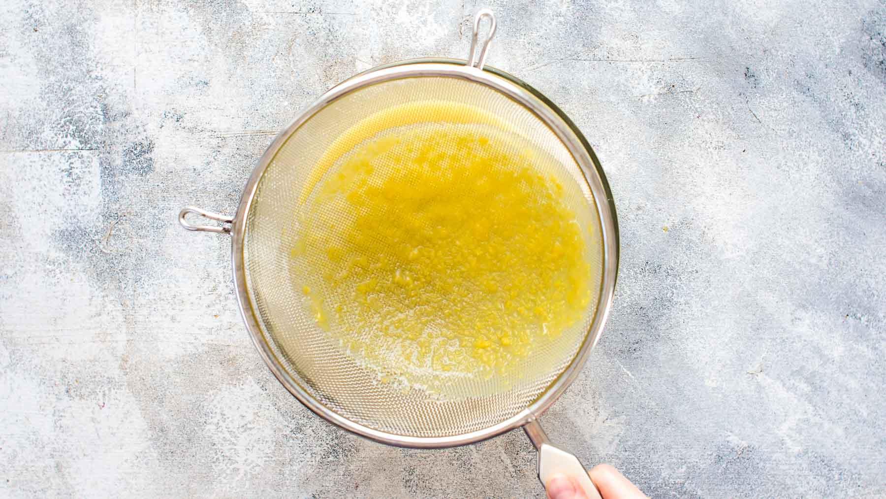 pouring the lemon filling through the mesh strainer