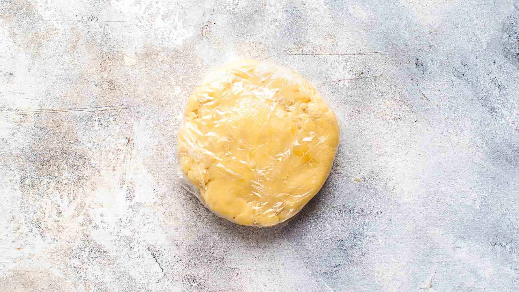 Tart crust dough shaped into a disc and wrapped in plastic