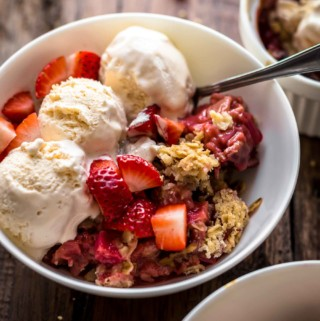 Strawberry Rhubarb Crisp with spoon in white bowl