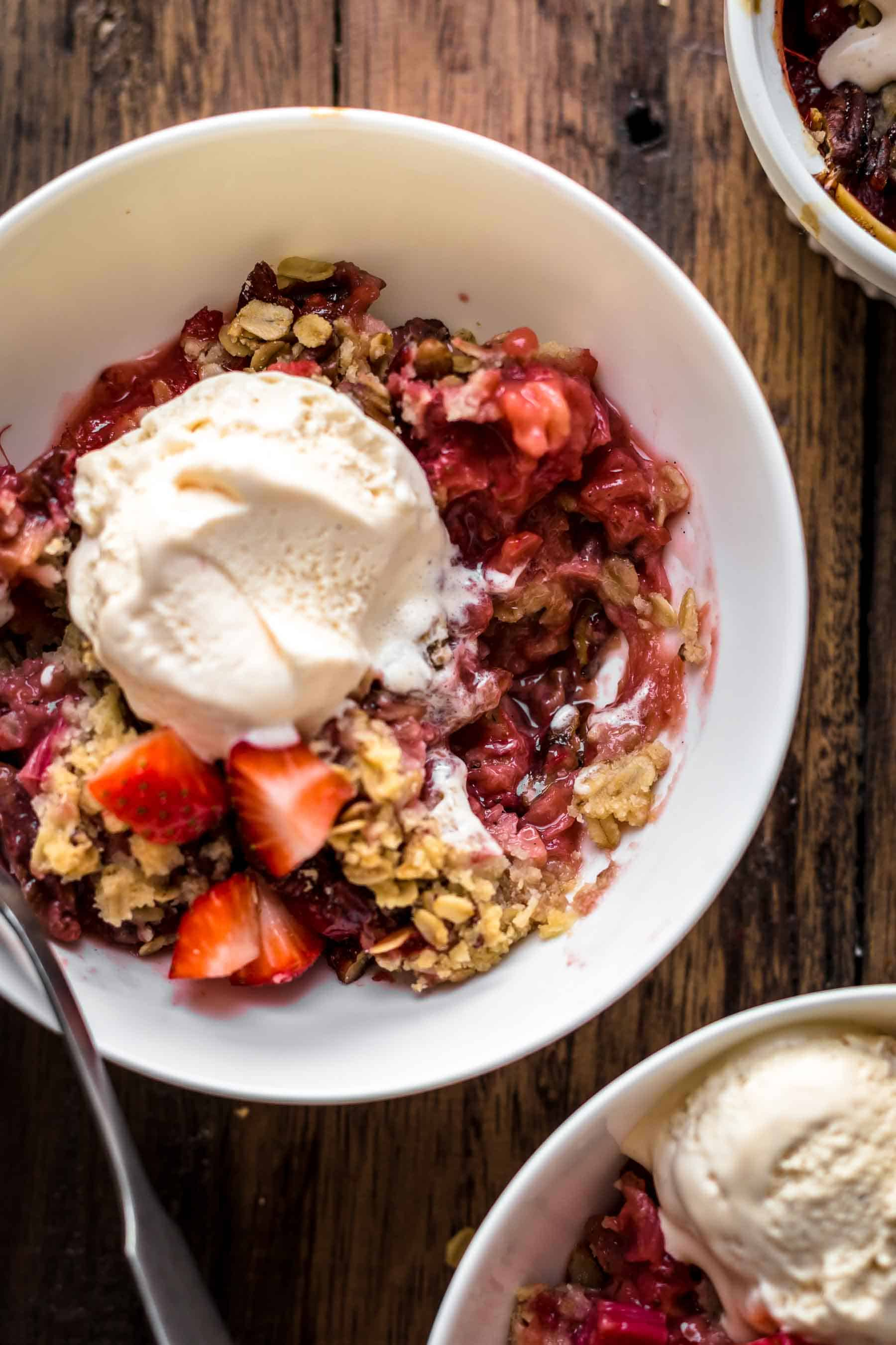 Strawberry Rhubarb Crisp with melted ice cream and spoon in white bowl