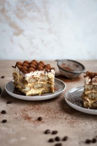 Styled Tiramisu slices on two grey plates