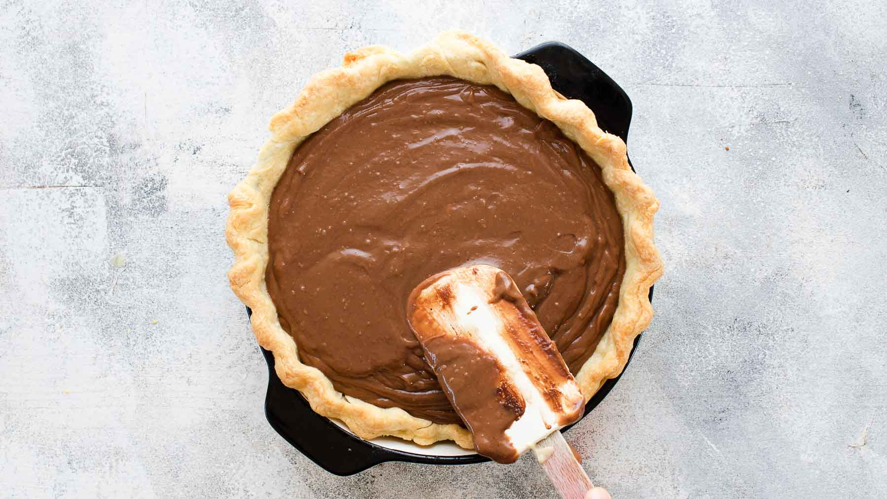 smoothing out chocolate cream pie filing into pie crust