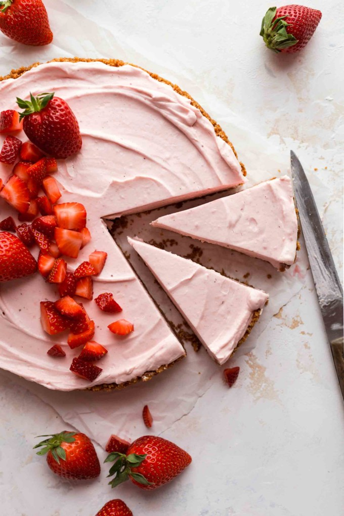two slices of pie cut with strawberries around the pie