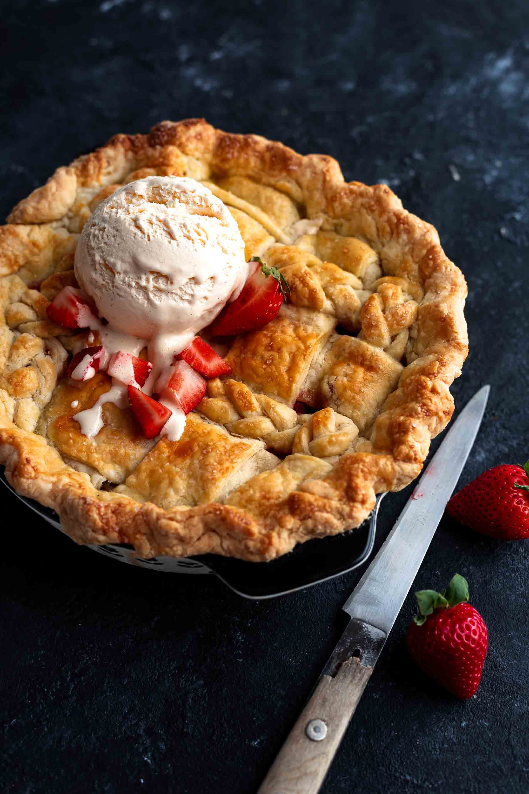 strawberry rhubarb pie with strawberries by it