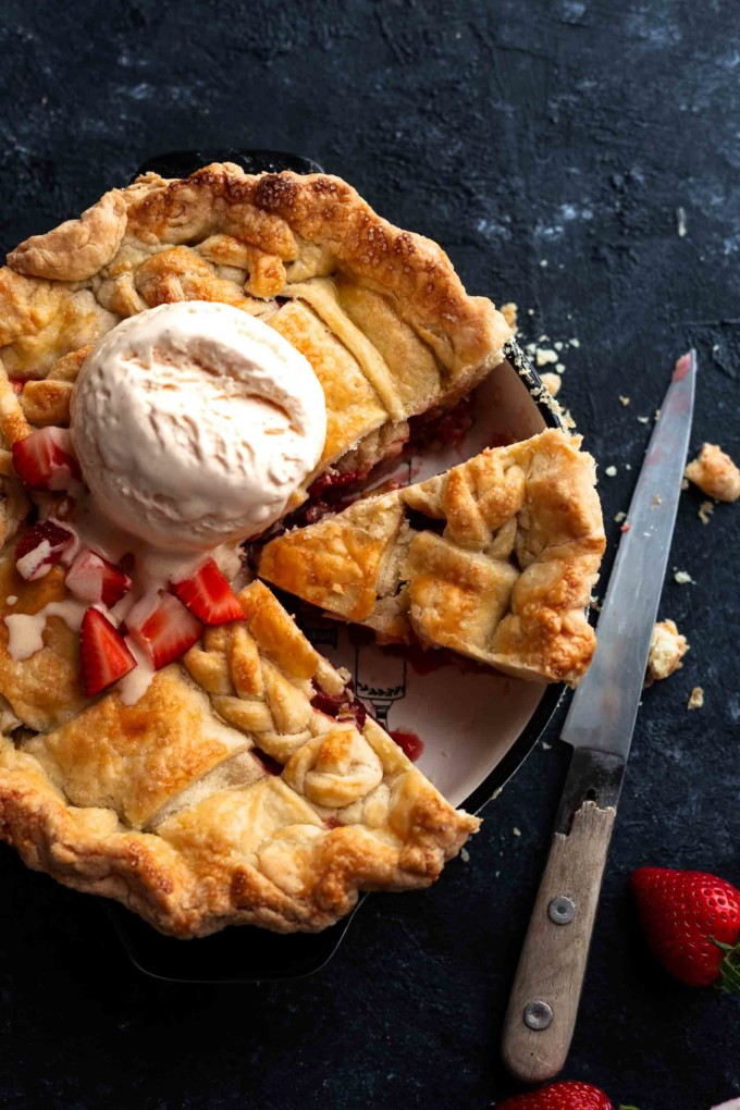 a whole strawberry rhubarb pie with ice cream dollop on it