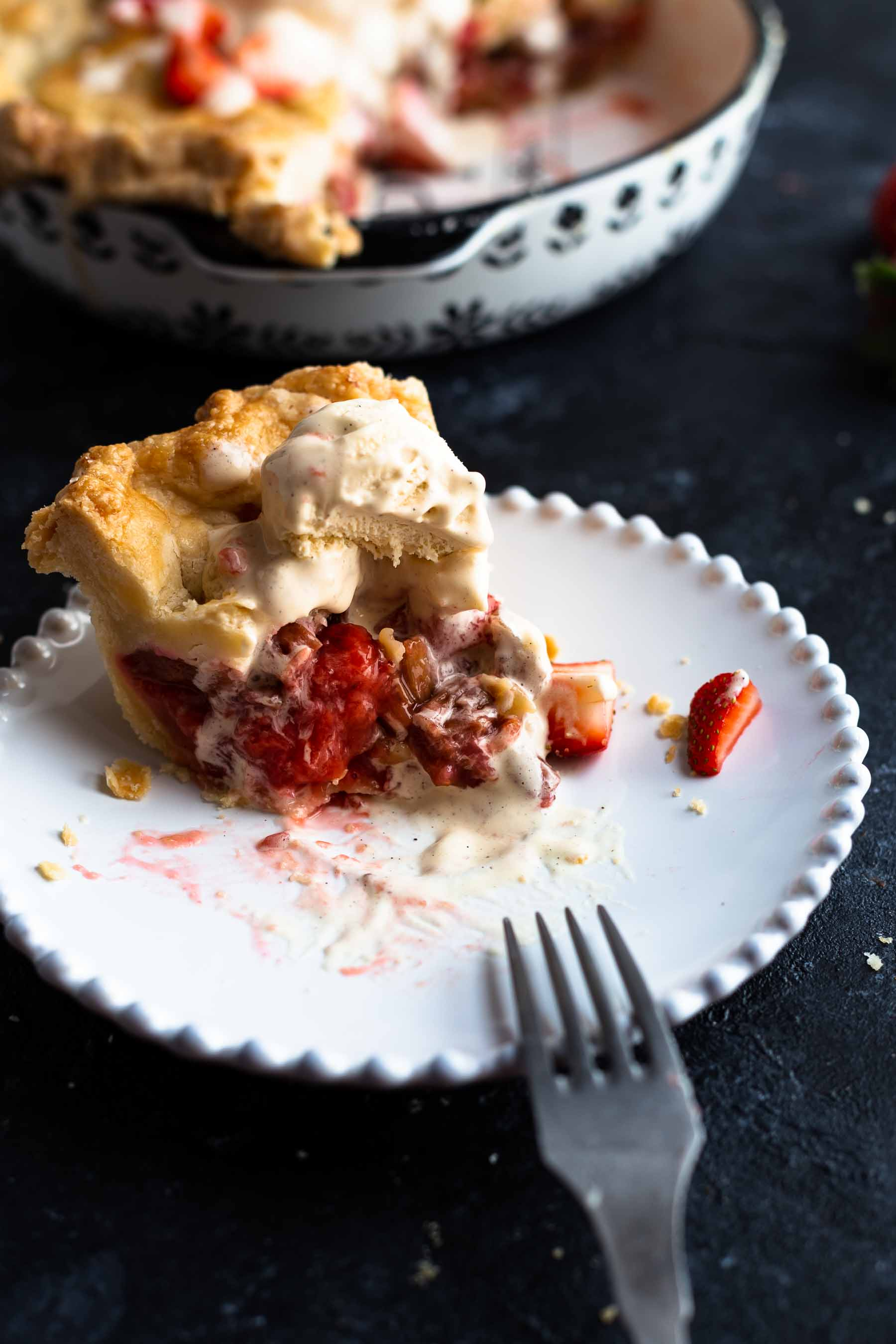 rhubarb strawberry pie on a plate with bite taken out