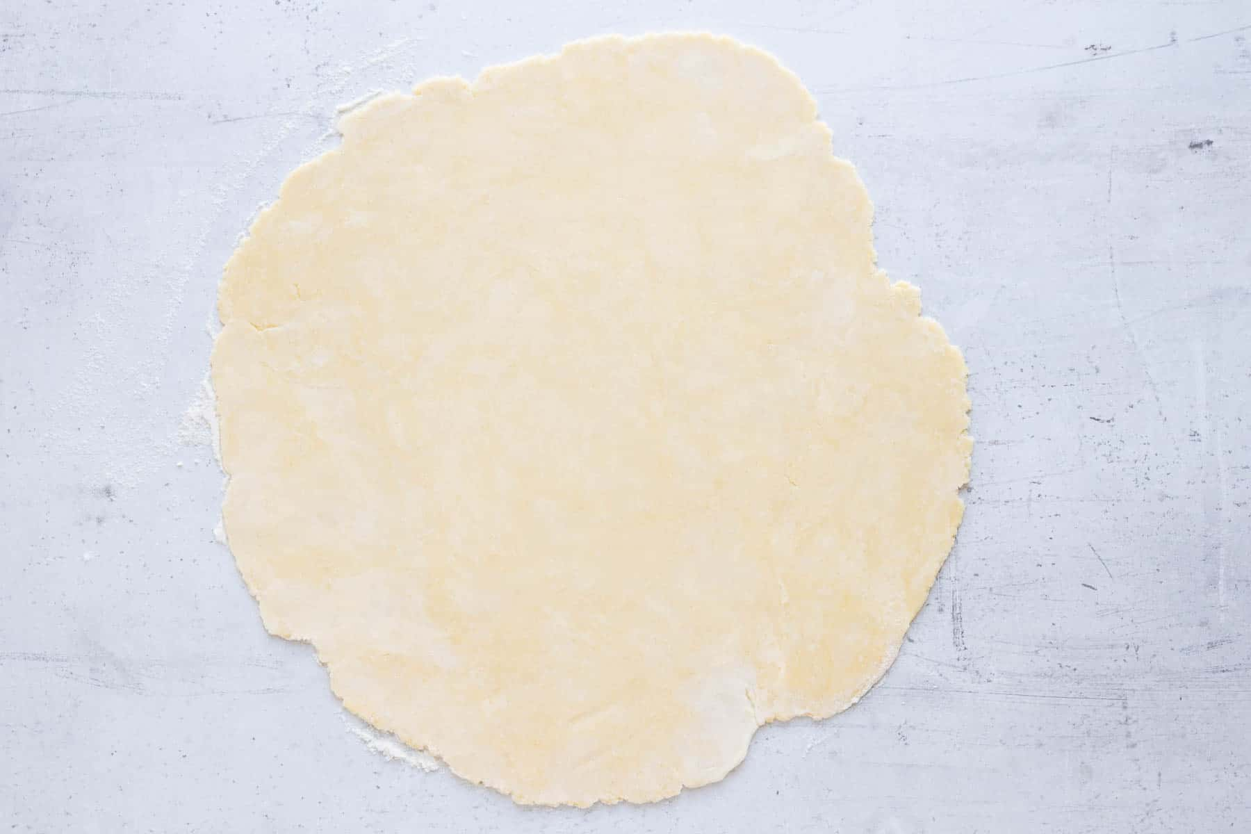 homemade pie crust rolled out on marble counter