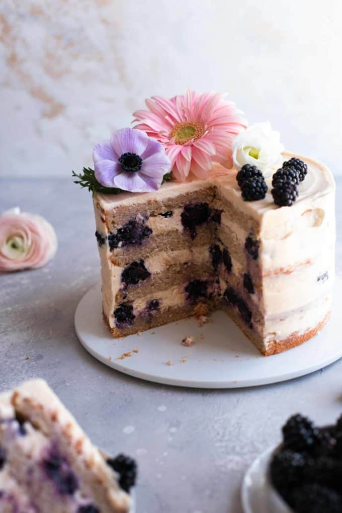 Blackberry cake with flower decoration on a serving plate that has a slice taken out