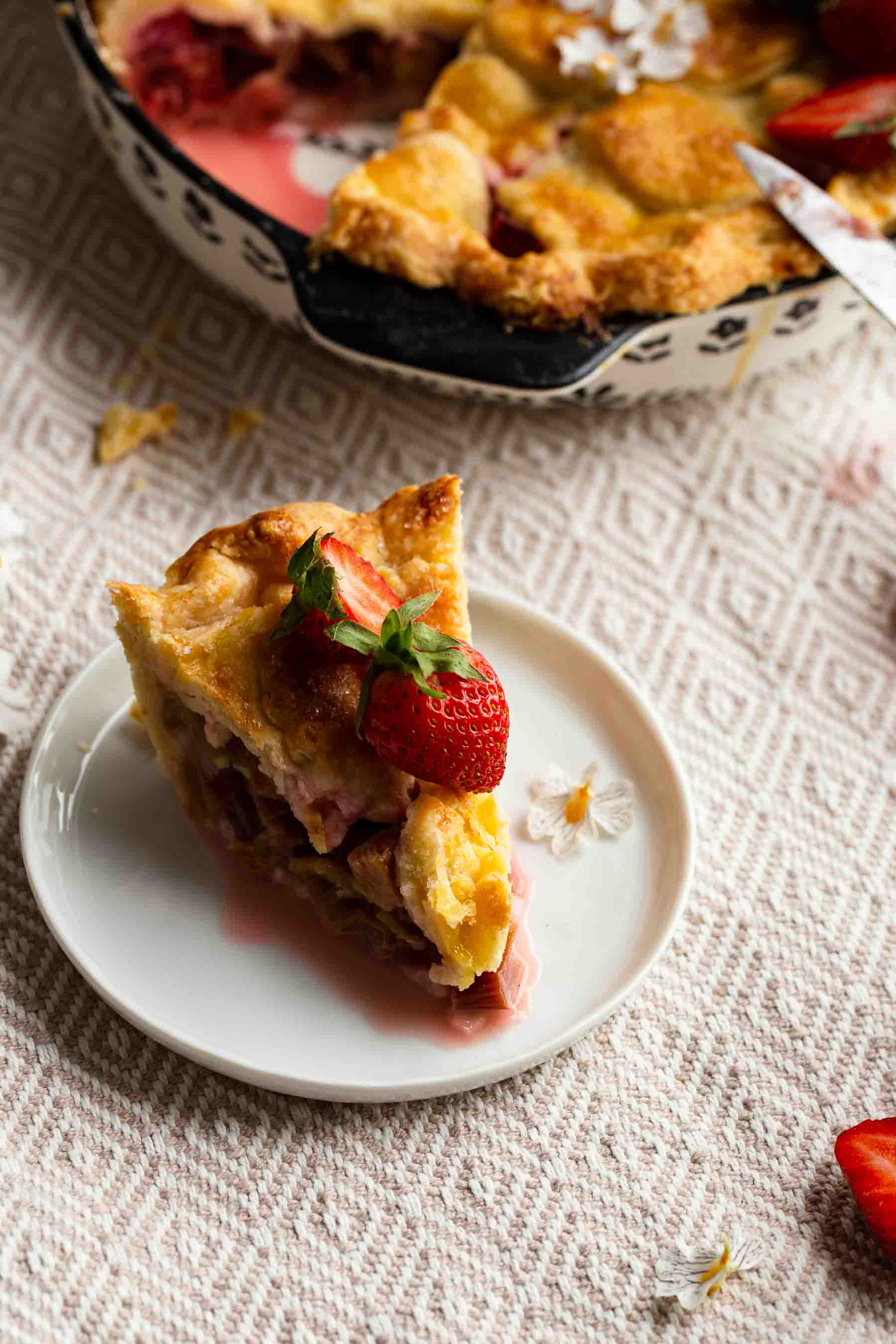 rhubarb pie on plate with strawberry on top