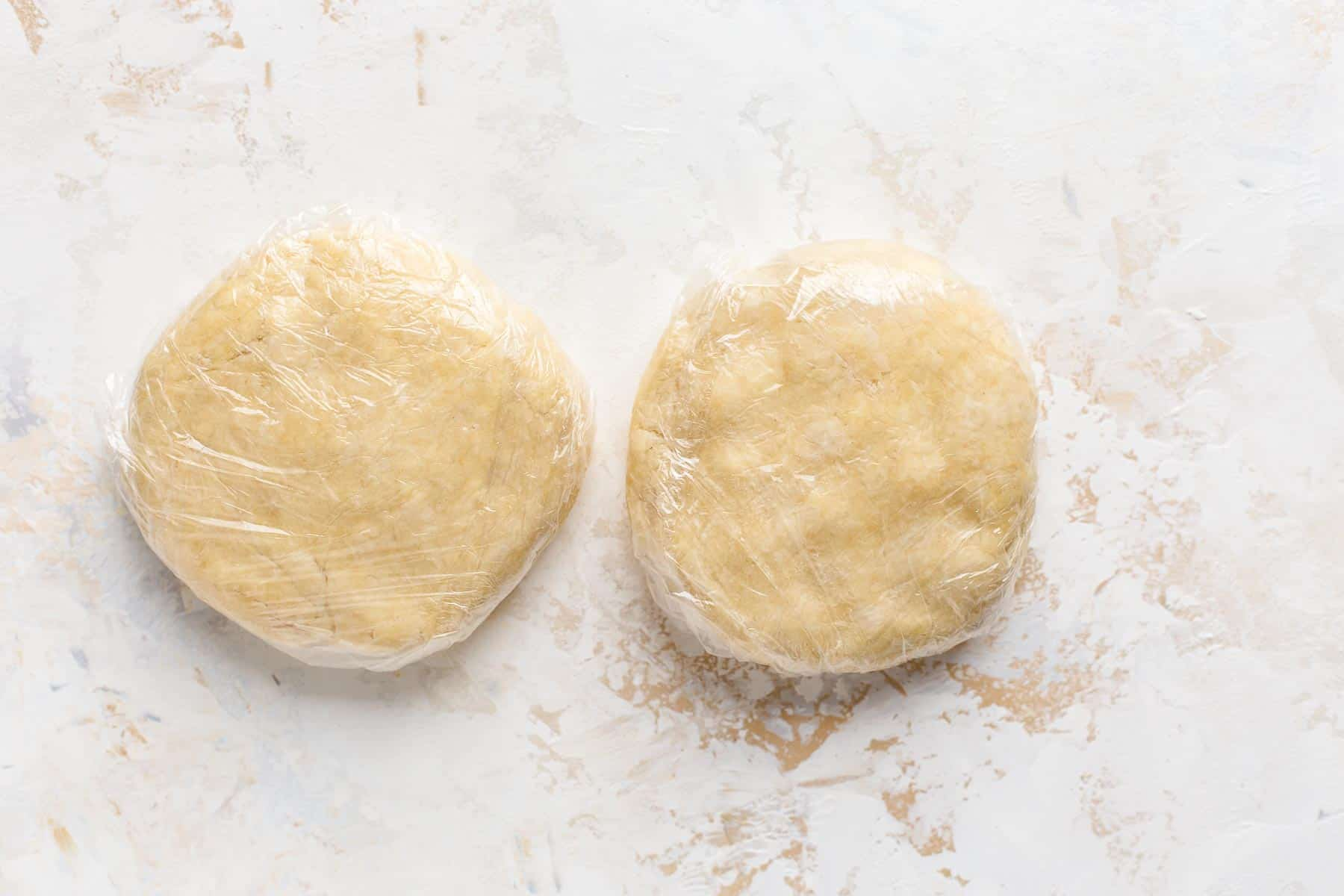 pie crust dough wrapped in plastic on counter
