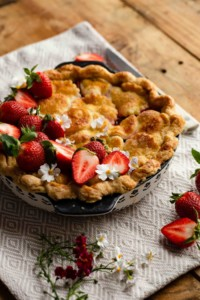 rhubarb pie with strawberries on top sitting on wooden table