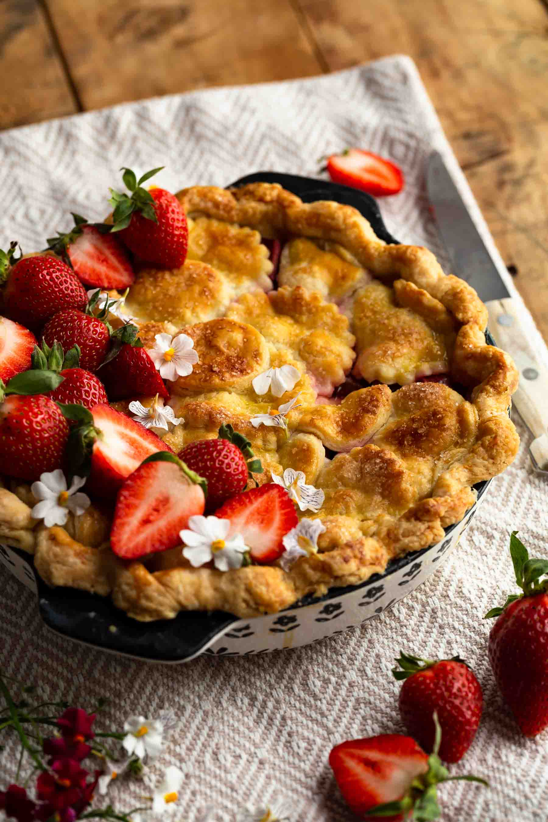 easy rhubarb pie on counter with strawberries on top