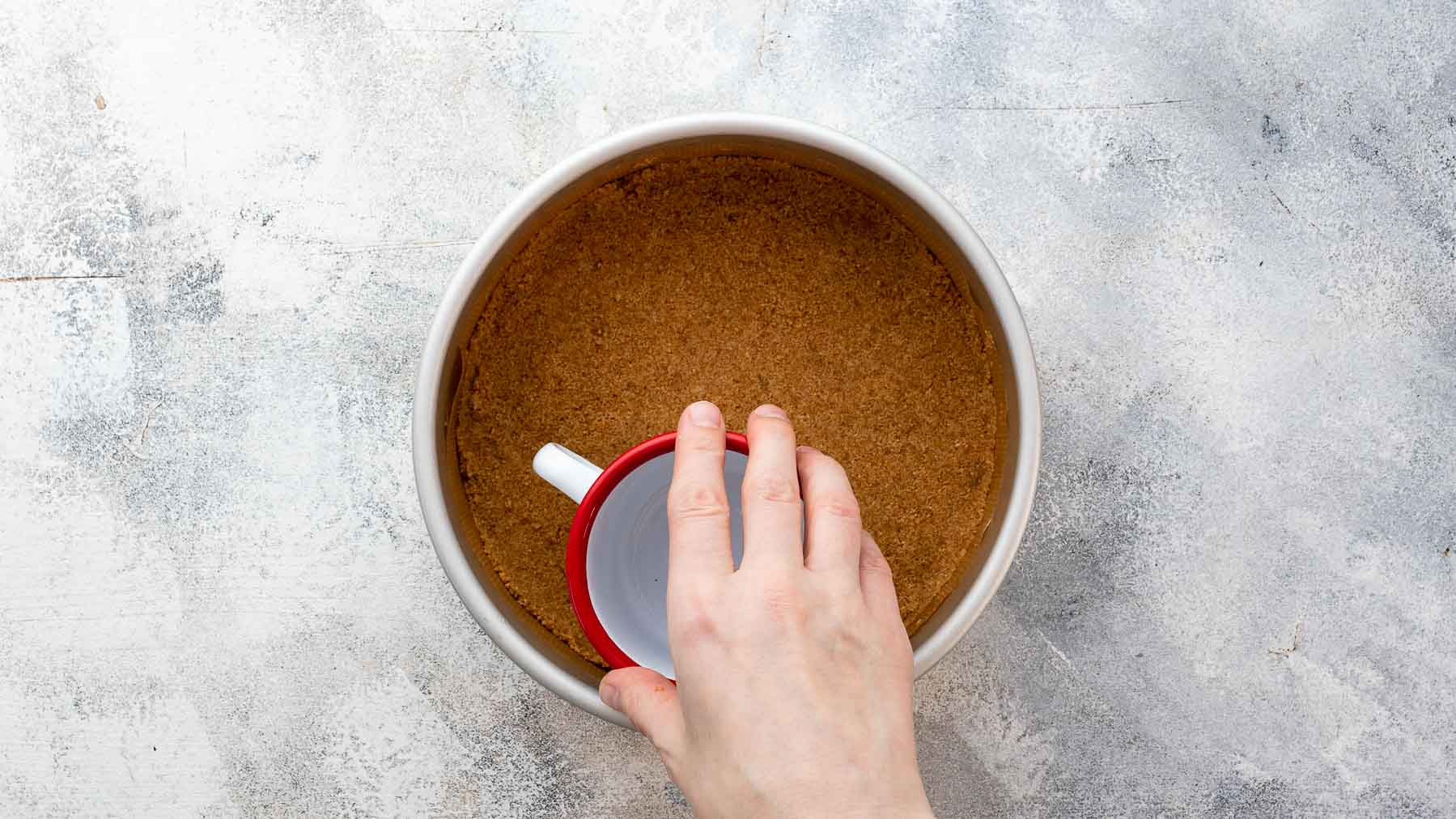 pressing graham cracker crust down in pan