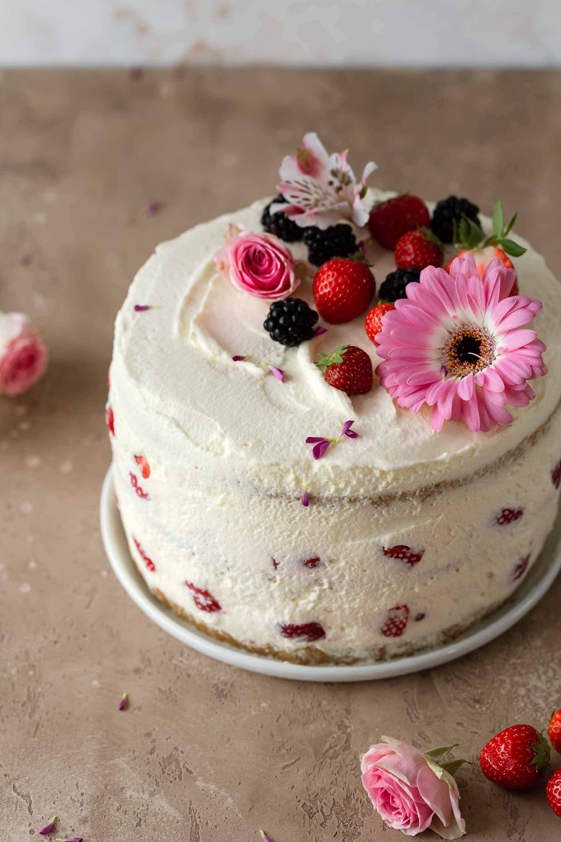 frosted layered strawberry cake with flowers on top