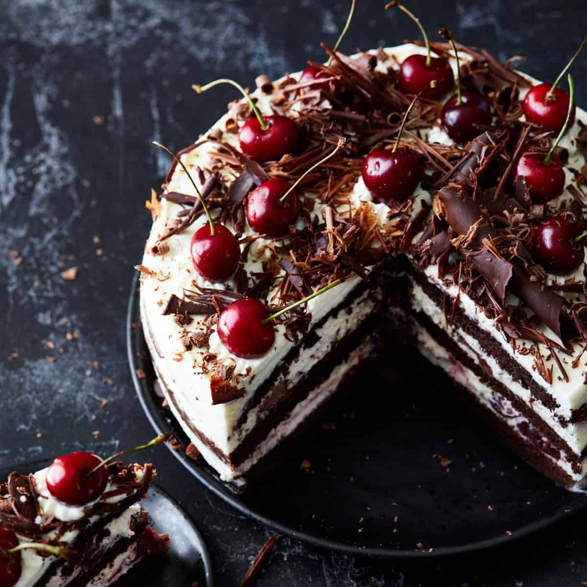 Baked and decorated Black Forest cake on a cake plate with a quarter of it missing
