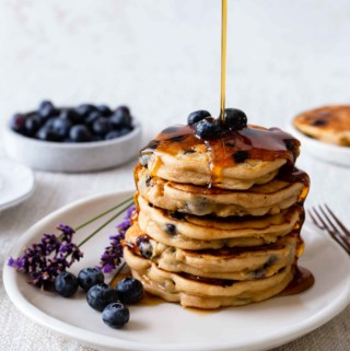 pouring syrup onto a stack of pancakes