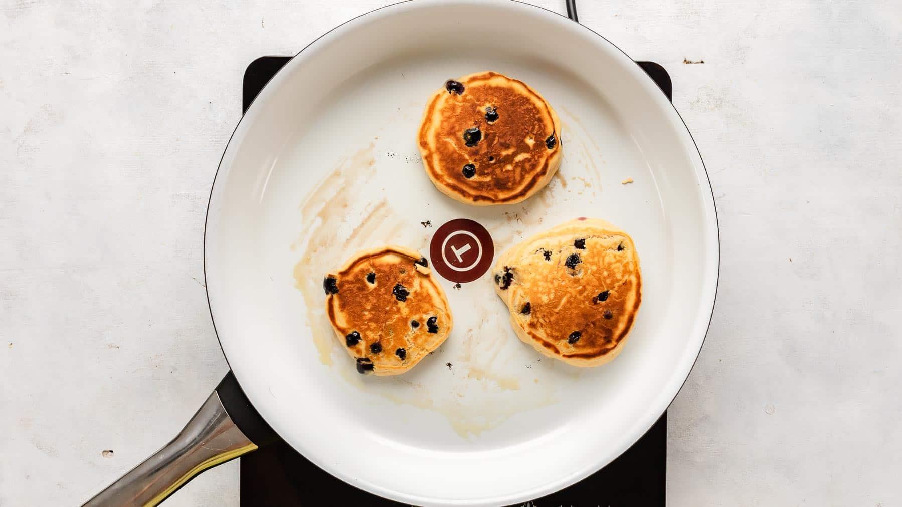 golden brown pancakes in pan